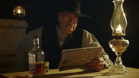 lampa naftowa : In a room lit by an oil lamp a cowboy from the American wild west era slowly draws his gun and hides it behind the newspaper he was reading. Wideo