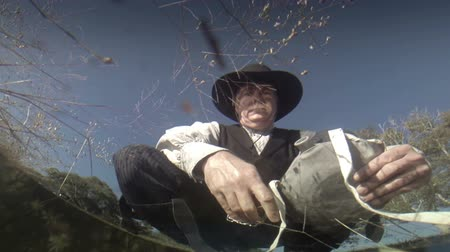 бдительный : As seen from below the surface of water in a pond a cowboy from the American wild west era armed with a pistol fills his canteen.