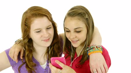 vöröshajú : Two pretty teenage girls who are best friends sharing listening to music on their smart phones. Isolated on white background