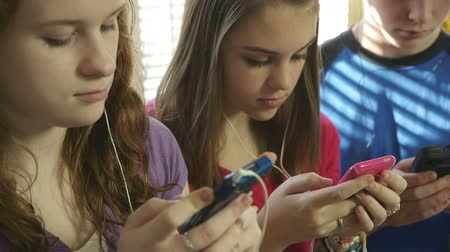 cimborák : Two pretty teenage girls listen to music while texting using their wireless smart phones.