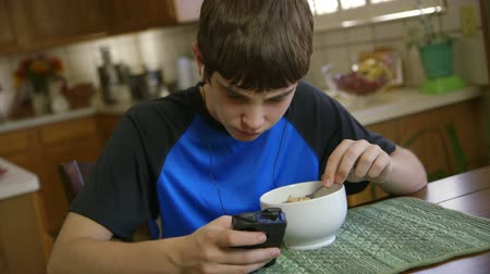 comer : With his smart phone a teenage boy listens to music and reads text messages while he eats breakfast.