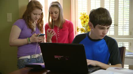ödev : A boy works on his laptop while two members of the project team stand in the background checking their phones.