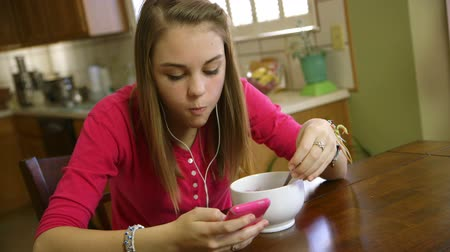 inseparable : A pretty teenage girl eating at a kitchen looks up from her smart phone and smiles at the camera Stock Footage