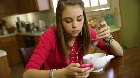 inseparable : A pretty teenage girl eating at the kitchen listens to music and reads text messages on her smart phone. Stock Footage