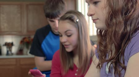 mozog e fel : Laptop and smart phone are in use as this scene moves up to the pretty smiling face of this teenage girl.