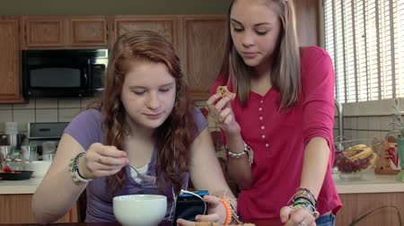 inseparable : Two teenage girls in a kitchen looking at a smart phone while snacking.