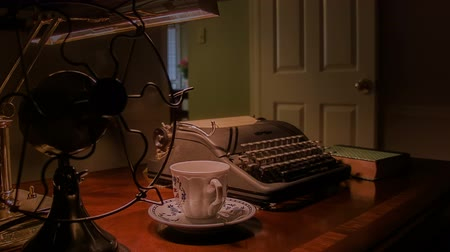 koflík na čaj : A vintage teacup and saucer on a desk with an old manual typewriter and electric fan in a dimly lit room.