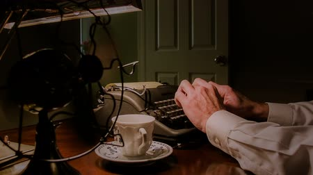 korszak : A vintage electric fan cools a man sitting in his office lit by the light from a single desk lamp typing on an old manual typewriter.