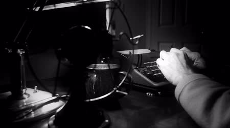 período : Through the turning blades of a vintage electric table fan a dimly lit Film Noir setting of a man typing on an old 1940 manual