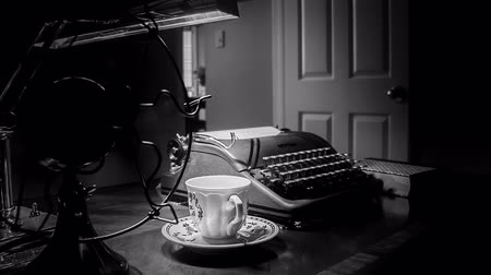 сбор винограда : Dimly lit Film Noir setting with teacup and saucer on a desk with an old manual typewriter and the turning blades of an electric fan.