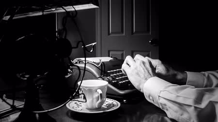maszyna do pisania : Dimly lit Film Noir setting of a man typing on a 1940 manual typewriter with an old electric fan and classic teacup and saucer close by.