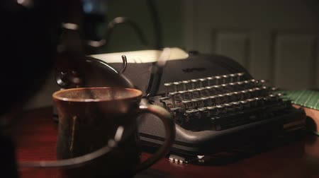 maszyna do pisania : Lit by lamplight of an old manual typewriter as seen through the turning blades of a vintage electric fan. Focus moves from fan to typewriter Wideo