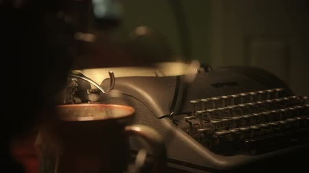 вентилятор : Lit by lamplight of an old manual typewriter as seen through the turning blades of a vintage electric fan. Scene tilts down and over. Стоковые видеозаписи