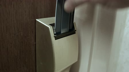 odemknout : A male hand using a typical hotel keycard to unlock his hotel room door.