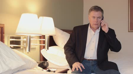 вводить : A mature handsome businessman in a hotel room sits on a bed while conducting business on his smart phone. Стоковые видеозаписи