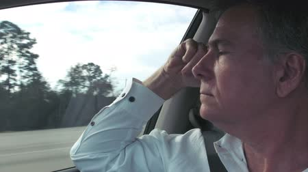 relaks : As a passenger in a moving vehicle this mature man is free to relax and think. Interior moving vehicle footage.