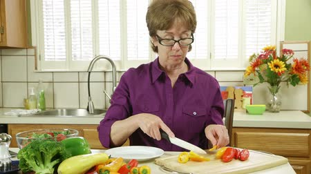 pimentas : An older woman working in her kitchen cutting up veggies.