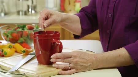 pimentas : The hands of a mature woman steeping a teabag in preparation of afternoon tea.