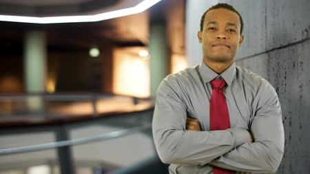 contentamento : A confident young African American businessman stands in the lobby of a modern office building. Stock Footage