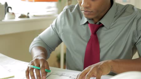 africký : An attractive young African American architect or engineer analyzing some plans in his office.