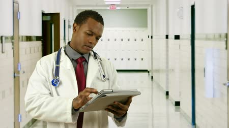 szpital : A young African American doctor in a hospital hallway working with an electronic or digital tablet pc looks up and smiles.