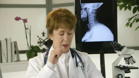 ona : A mature female doctor sitting in her office turns from reviewing an x-ray image on a monitor screen looking pensive before she starts making notes.