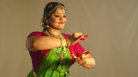 головной убор : A lovely young woman using traditional mudra or hand gestures to tell a story during classical Indian dance.