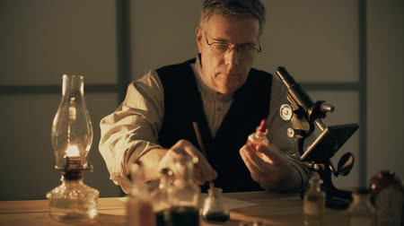egészségügy és az orvostudomány : turn of the century scientist looking at a chemical and taking notes 4k Stock mozgókép