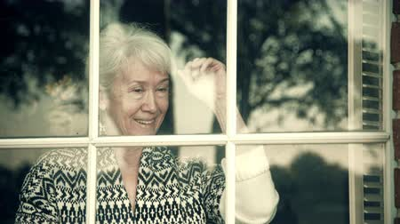 uplifted : An elderly woman looking through a window becomes happy to see whom she has been waiting for finally arrive 4k