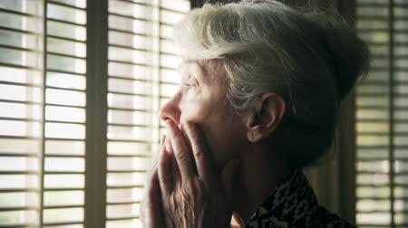 watching : An anxious elderly woman looking through the shutters on her window.