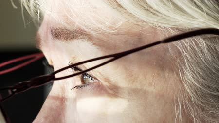 wzrok : Slow motion close up of the eyes of an old Caucasian woman who puts on her glasses to see better. Wideo