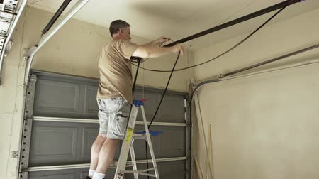 opravář : Homeowner replacing the belt on his home automatic garage door opener 4k