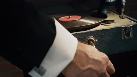 old times : Dramatic lighting on this old 1920s style phonograph being cranked up and the needle placed on the record. Stock Footage