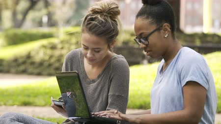 two college girls studying outside turn to look at someone 4k
