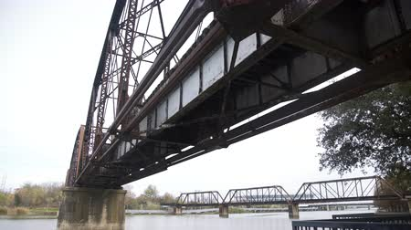 underside view of old train bridge over brazos river 4k Stok Video