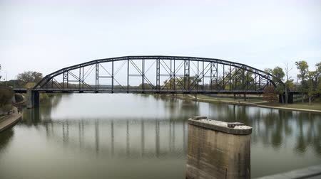 cars driving over an old truss bridge on the brazos river waco