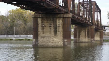 underside view of rusted train bridge on the brazos river 4k Stok Video
