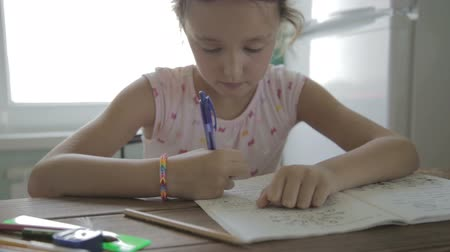 домашнее задание : Little girl is doing his homework for elementary school.