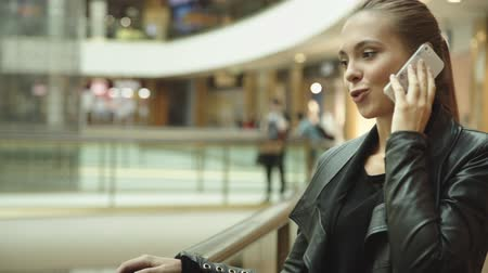 uzun saçlı : Beautiful girl with long hair, talking on the phone in the mall Stok Video