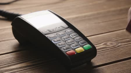 плата : Mans hand pushing the button and swipe credit card payment on pos terminal standing on wooden desk. Transactions at the credit card terminal. Payment with credit card through terminal. Close-up shot Стоковые видеозаписи