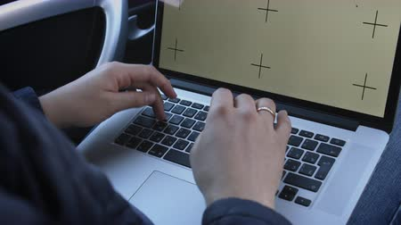 Saint Petersburg, Russia - March 24, 2017 Mans hands using Apple MacBook laptop with screen template sitting behind the wheel of car. Crop close-up shot.