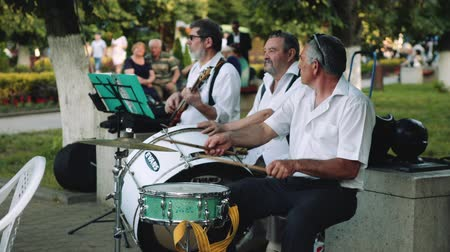 Armavir, Russia - May 31, 2017: Men play musical instruments in the street orchestra in the park on open air