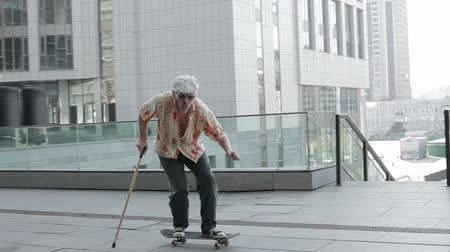 travessura : Old man with a cane riding on a skateboard.