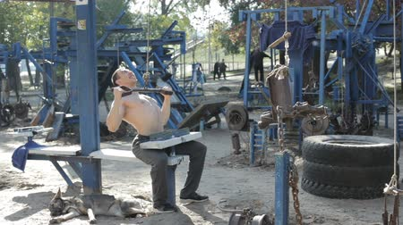 self made : In the park on self-made simulators a man trains, he strengthens his muscles. Stock Footage