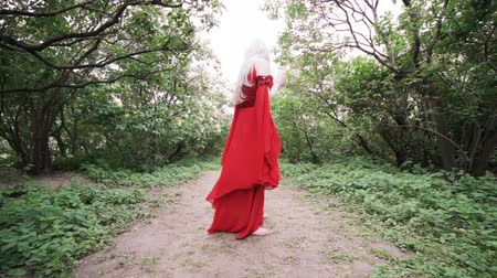 witchcraft : Woman in a red dress is dancing in the garden.