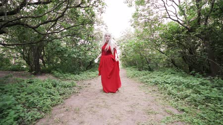 enchanted princess : Woman in a red dress whirls in a dance in the forest.
