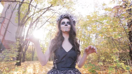 frightful : Beautiful zombie girl with a makeup mask in the autumn forest. Halloween holiday.