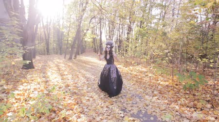 frightful : Zombie girl walks through the autumn forest. Halloween holiday dressing up