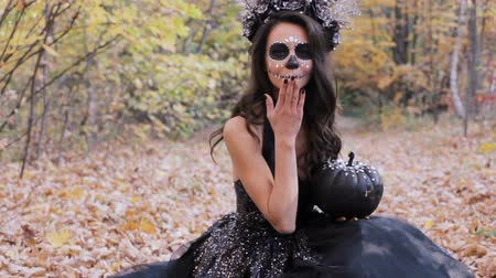 frightful : Beautiful zombie woman with pumpkin in the autumn forest. She is ready for pravzhnik Halloween. Stock Footage