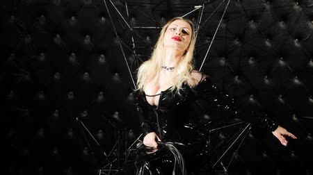 Woman on a throne with a whip, wearing a latex suit. She demonstrates the style of BDSM.